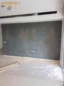 קיר של בית בשיפוץ לאחר ביצוע שיוף והחלקת הקיר
